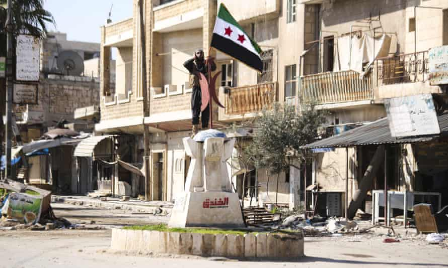 An opposition fighter raises a flag on the rubble-strewn streets of Saraqib.