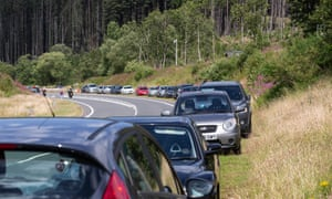 Cars parked alongside the road as members of the public walk Pen y Fan, South Wales highest mountain in Brecon. High temperatures are forecast across the UK today, with some areas in the south expected to reach 33-34C.