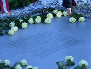 Flowers are placed on a memorial plate at Buchenwald concentration camp