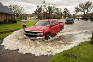 Vehicles are driven through a flooded street after Hurricane Ida passed through in LaPlace, La.