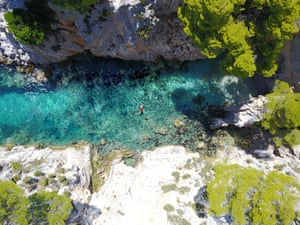 Aerial view of a swimmer lying on his back in a river on Skopelos Island, Greece.