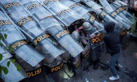 A demonstrator clashes with police during a protest against the Indonesia government's job creation bill in Bandung, West Java.