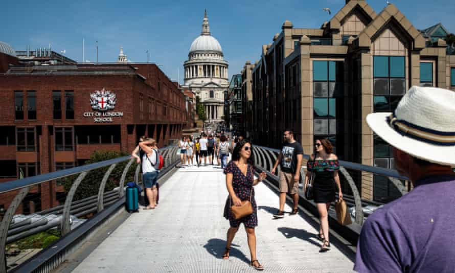 People cross the Millennium Bridge on a sunny day in central London