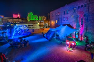The yard at night, including a neon head artwork.