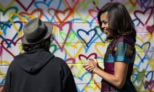 Washington, US To celebrate International Women's Day, first lady Michelle Obama talks to artist Mr. Brainwash during a live painting of a Let Girls Learn mural at Union Market