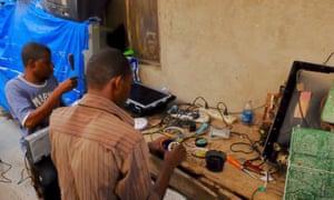 Two men, working in Zanzibar market, repair imported TVs from Europe