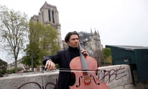 A musician plays near Notre Dame Cathedral the day after the fire.