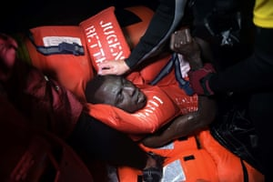 A migrant is rescued after the rubber boat that he was in began to sink some eight nautical miles off the coast of Libya