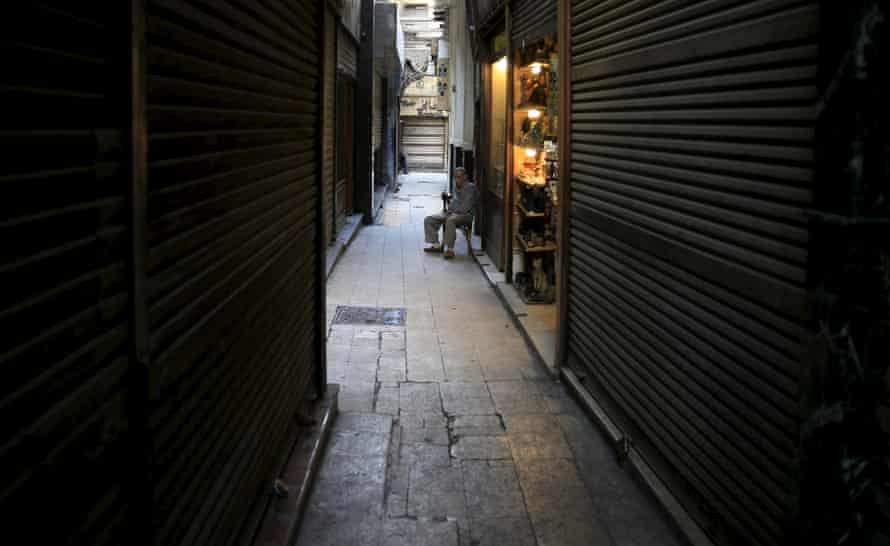 A shopkeeper looks out for customers near rows of closed shops in the Khan el-Khalili market, Cairo.