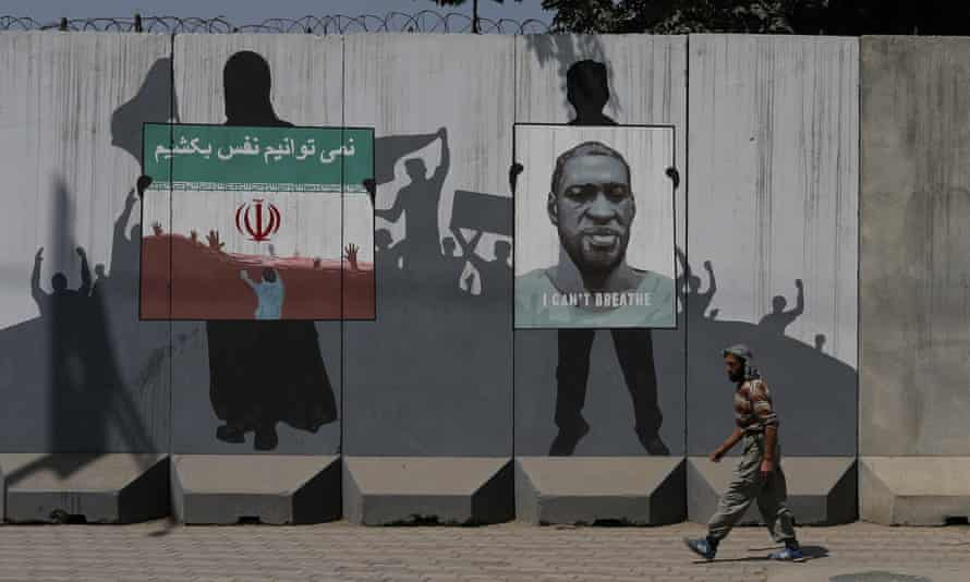Murals in Kabul depict an Iranian flag showing people drowning with text reading 'We can't breathe' in Persian next to a picture of George Floyd.