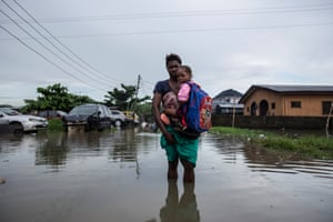 Woman holding her children in knee-high floodwater