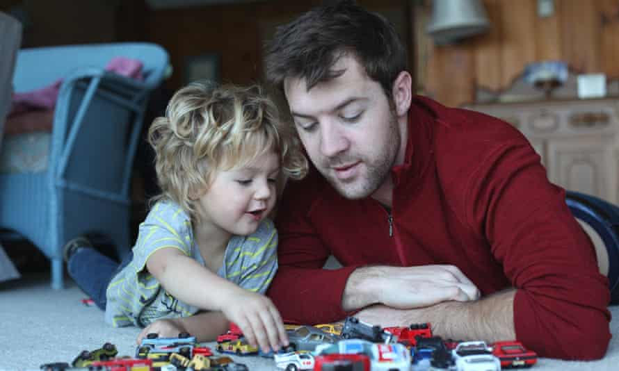 Father and toddler daughter playing with toy cars in sitting roomTITLE