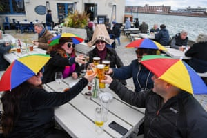 Members of the public enjoy a drink outside at The Still & West pub at Spice Island in Portsmouth, England.