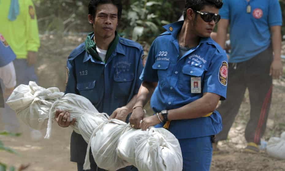 Rescue workers carry a body bag with remains retrieved from a mass grave in Thailand's southern Songkhla province.