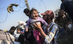 A Syrian man fleeing the war carries a child over the border into Turkey.