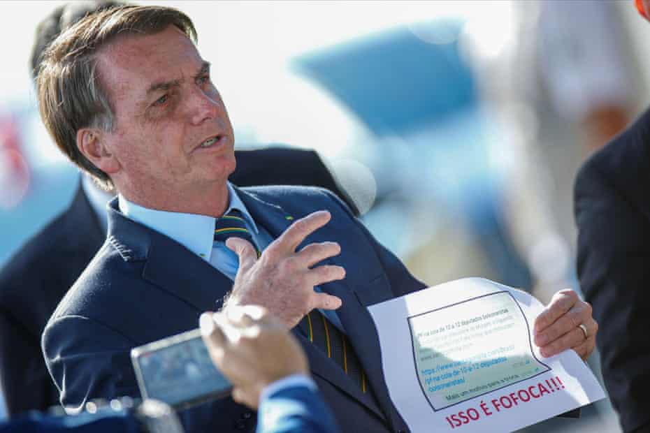 Brazil's president Jair Bolsonaro with a printout of an opponent's WhatsApp message about him.