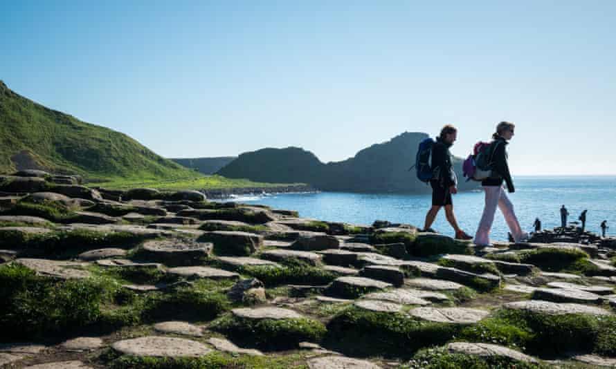 Giant's Causeway in Northern IrelandBushmills, Northern Ireland, U.K. - June 7, 2013: Visitors wearing backpacks walk on the geologically unique coastline