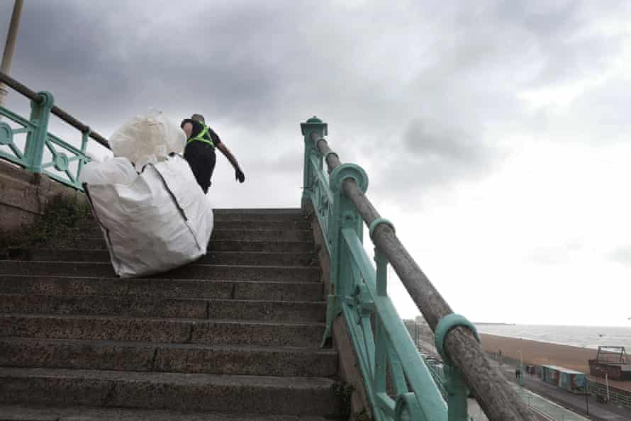 Rob dragging a large bag up stairs on Brighton seafront.