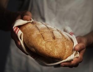 Baker holding warm bread
