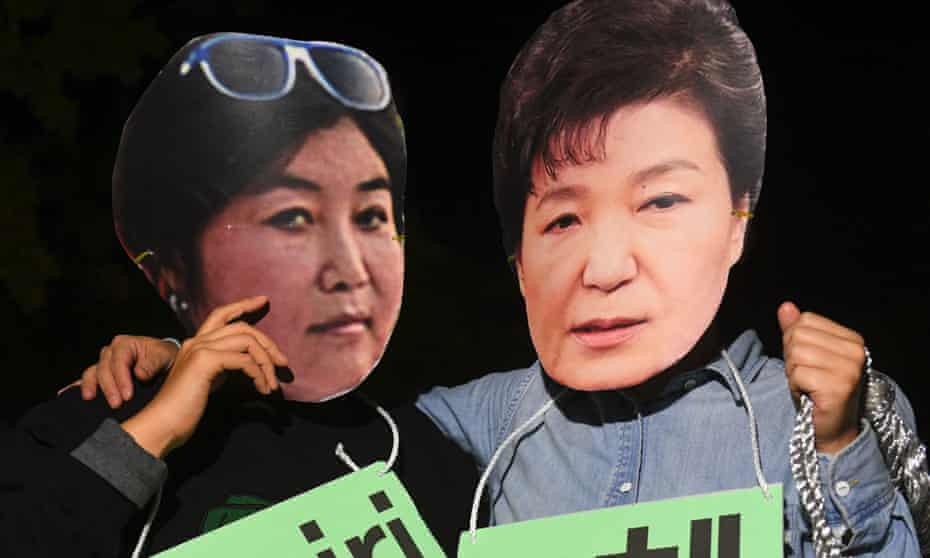 Protesters in Seoul wear masks depicting South Korean president Park Geun-hye, right, and her confidante Choi Soon-sil