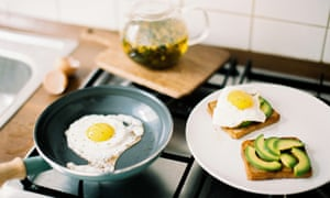 Breakfast: egg frying in a pan on the stove at the kitchen at home