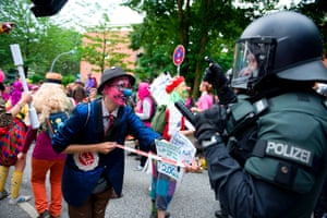 Demonstrators dressed as clowns face police officers as they take part in the BlockG20 – Colour the Red Zone protest