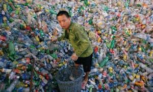 A Vietnamese man works recycling plastic bottles at Xa Cau village outside Hanoi, Vietnam