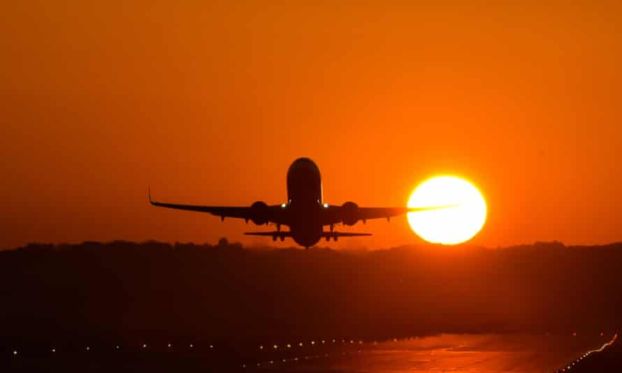 Plane taking off into sunset