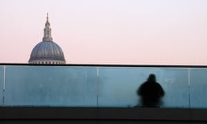 A homeless man sitting on Millenium Bridge, St. Paul's Cathedral dome in the background, London, England, UK.