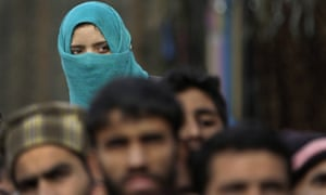 A Kashmiri woman watches the funeral procession of Noor Mohammad Tantray, the leader of the Pakistan-based militant group Jaish-e-Mohammad.