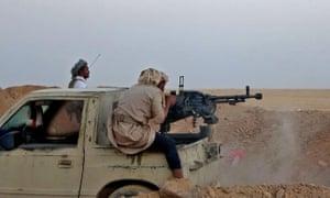A combatant fires a heavy machine gun