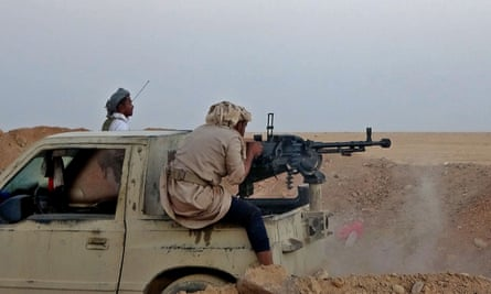 A combatant fires a heavy machine gun during clashes between Yemen's Saudi-backed government and Houthi rebel fighters.