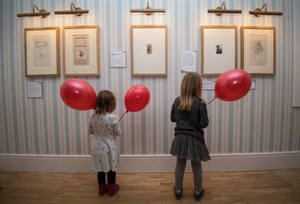Young girls look at original Winnie-the-Pooh pencil drawings by EH Shepard.