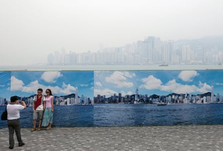 Tourists from mainland China take photos in front of a large banner showing what Hong Kong looks like on a rare clean air day.