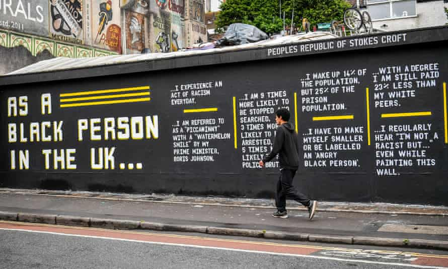A man walks past street art by Lanie Rose and @asablackpersonintheuk in Stokes Croft, Bristol.