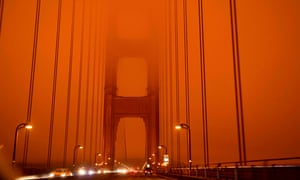 Cars drive along the Golden Gate Bridge under an orange smoke-filled sky – at midday in San Francisco.