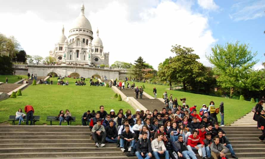 A school group of teenagers pose for a snapshot in front of the Sacre-Coeur in Paris.