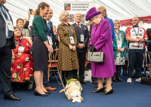 "Queen Elizabeth II meets RBLI volunteer Kate Bosley while her guide dog ""Phoenix"" sleeps on the floor between them during a visit to the Royal British Legion Industries village in Aylesford, Kent"