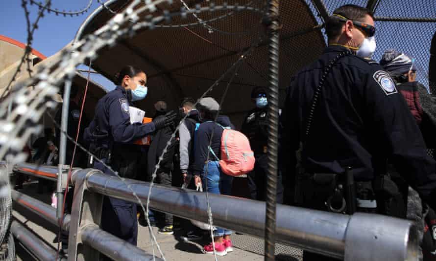 US police supervise migrants near Ciudad Juarez, Mexico.