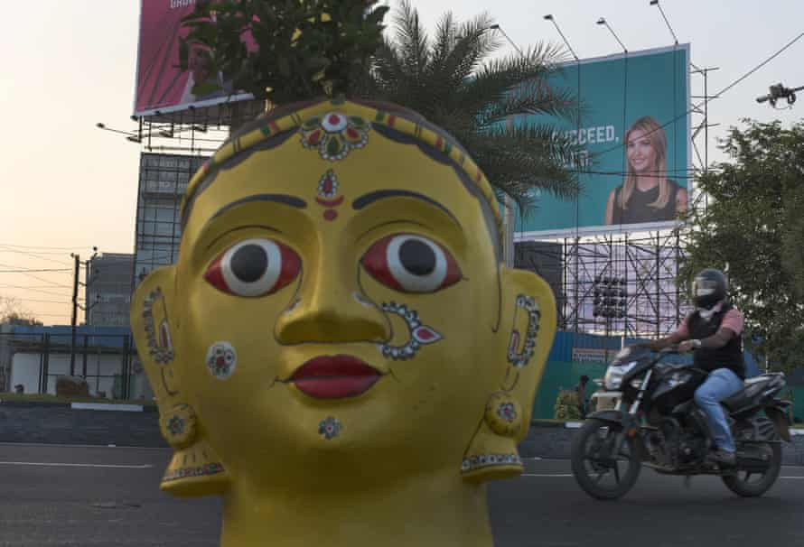 A motorist rides past a billboard poster of Ivanka Trump as a statue is erected at the entrance of the summit in Hyderabad.