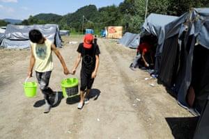 Migrants carry water in makeshift camp near Croatian border in Velika Kladusa, Bosnia and Herzegovina