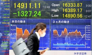 Young Japanese woman walking past stock market board
