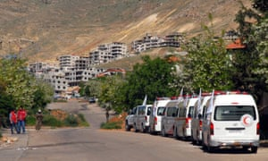 Ambulances of the Syrian Arab Red Crescent wait on the outskirts of the rebel-held town of Madaya on 20 April 2016
