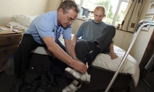 Homecare worker helping a client put his shoes on