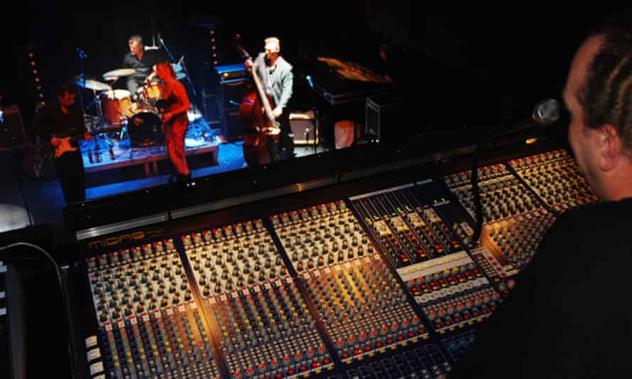 A sound technician behind mixing board during a concert
