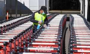 An airport worker cleans airport trolleys for passengers arriving at the International Airport Terminal in Sydney, Australia.