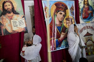 Women swaddled in traditional white garb waited for their child's turn to be blessed. Images of Jesus and Mary adorn the walls, on flimsy posters adorned with scripture in Tigrinya