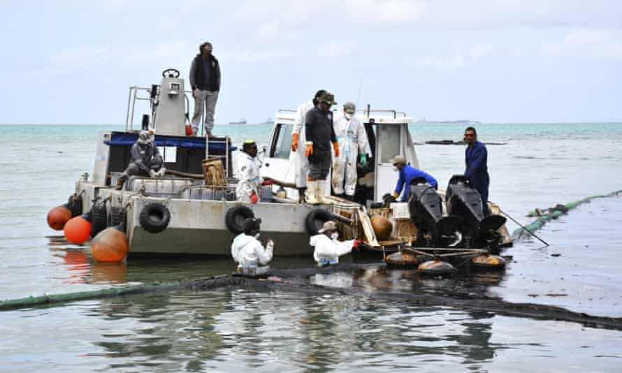 Workers try to prevent the spread of oil in Mahebourg, Mauritius.