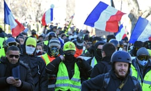 "People, some with masks, march with French national flags in the background during an anti-government demonstration by the Yellow Vests ""Gilets Jaunes"" movement."