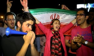 A woman holds up an Iranian flag as people celebrate a landmark nuclear deal, in Tehran on Tuesday night.